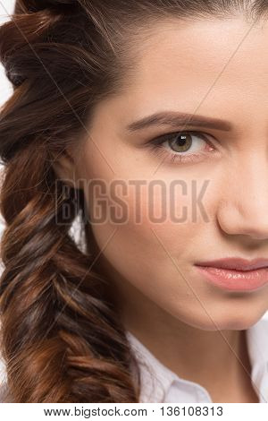Closeup portrait of half face of woman in studio. Lady with creative braid hairstyle. Hairstyle. Beauty glamour fashion model girl portrait. Perfect skin and makeup.