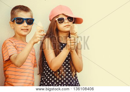 Kids eating gelato and soft serve ice cream. Boy and little girl in sunglasses enjoying summer holidays vacation. Instagram filter.