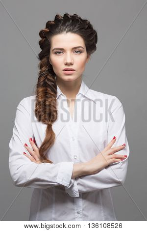 Portrait of pretty model woman with braids over grey background. Female in white blouse with modern hairstyle in studio.