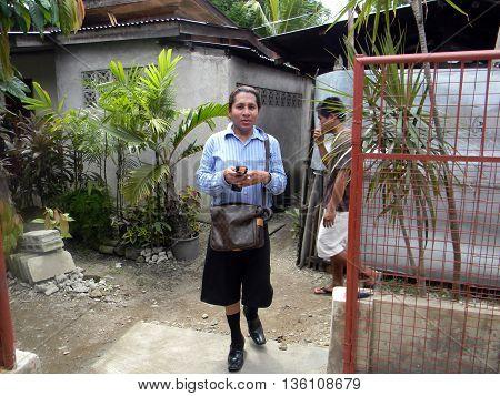 CEBU CITY, CEBU / PHILIPPINES - JULY 29, 2011: A man with a cellular telephone and a shoulder bag walks through an alley in Cebu City.