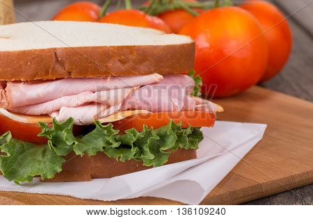 Closeup of a ham sandwich with cheese tomato and lettuce
