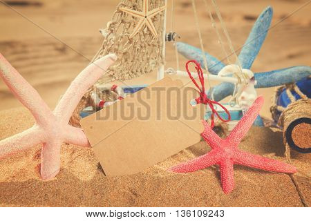 empty paper note with starfish frame on sandy beach, retro toned