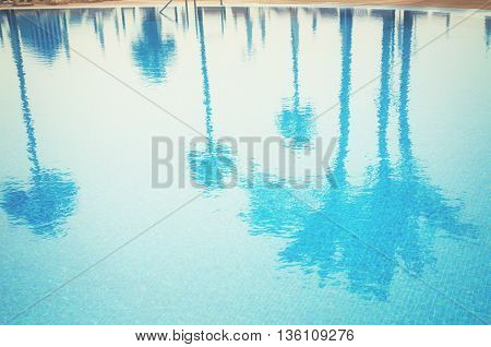 blue cool pool with reflections of palm trees, retro toned