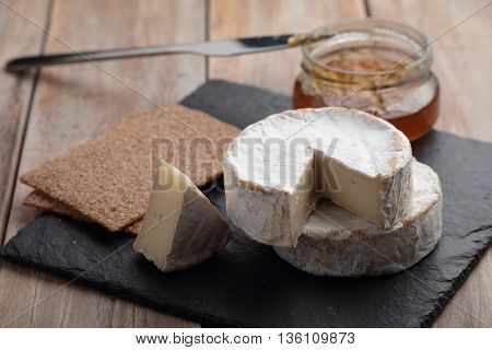 Camembert cheese, jam, and crispbread on a rustic table