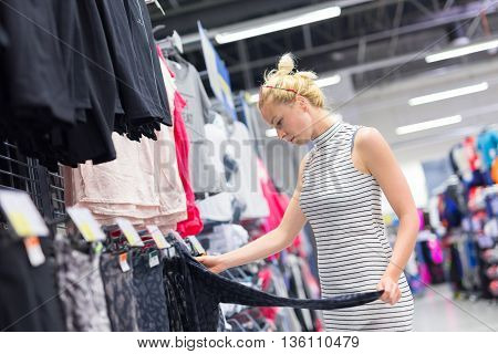 Beautiful caucasian woman shopping sportswear in sports store.
