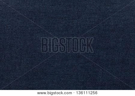 Dark blue background from a textile material. Fabric with natural texture. Cloth backdrop.