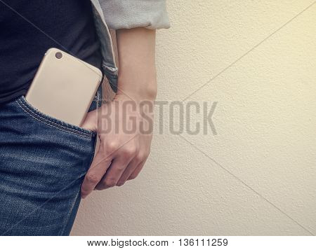 Close up of mobile phone in jeans pocket with poses hand of a person standing against the wall with copy space and Vintage filter
