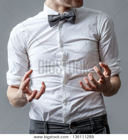 Man in a white shirt with a gray bow tie. Aggression and anger hand gestures.