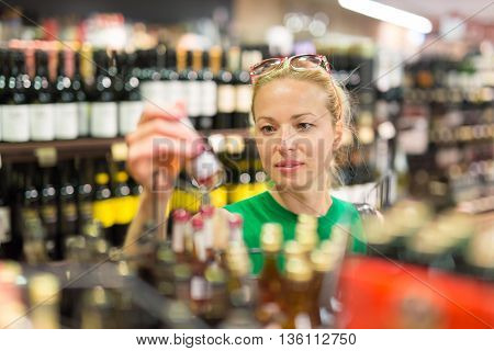 Beautiful caucasian woman shopping groceries at supermarket.