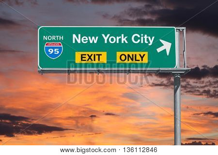 New York City exit only highway sign with sunrise sky.
