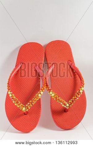A pair of red womens sandals with sequins and beaded decorations.