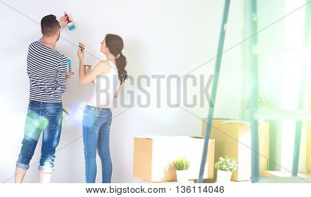 Portrait of happy smiling young couple  painting interior wall of new house