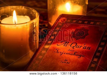 The cover of holy Koran (Indonesian translated version) with candles providing glimmering warm light.