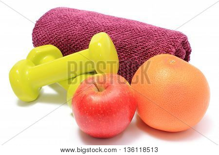 Fresh fruits apple grapefruit purple towel and green dumbbells for using in fitness concept for healthy nutrition and lifestyle