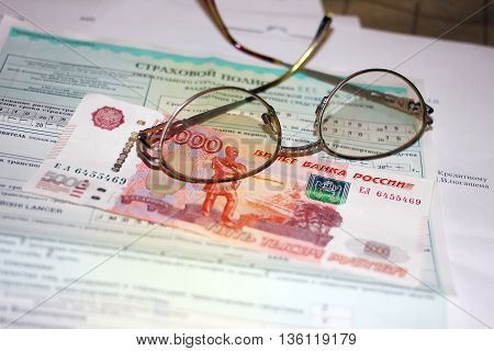 Russian money, glasses and papers for auto insurance