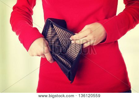 Young woman shows her empty wallet.