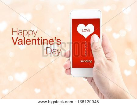 Hand Holding Smartphone With Sending Word And Heart Shape On Screen On Light Bokeh Background, Happy