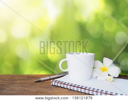 White cup of coffee pen and notepad on wooden table over green bokeh background