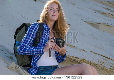 Young beautiful woman backpacker with red hair and freckles traveling in the desert and making pictures with vintage film camera. Sandy dunes background. Travel adventure freedom concept. Toned.
