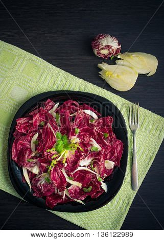 Vegetable salad with endive and fennel fresh and healthy on dark wooden background with fork. Vegetarian Food. Healthy food. Dietary meal. Top view.