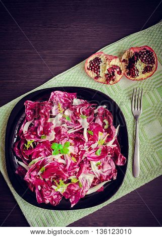 Easy diet chicory salad with pomegranate on dark wooden background with fork. Italian bitter red chicory radicchio salad. Vegetarian Food. Healthy food. Dietary meal. Top view copy space vertical