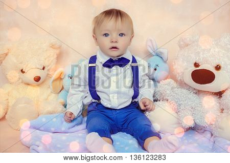 Handsome little gentleman wearing the bow tie and suspenders sitting with Teddy Bears. Little baby boy looking confusedly with funny face. Romantic and love concept. Children portrait.