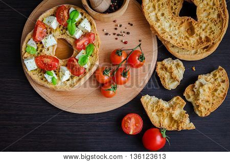Italian appetizer Friselle. Italian dried bread Friselle on wooden board with tomatoes cherry basil and pepper. Italian food. Healthy vegetarian food. A quick and easy snack for party time.