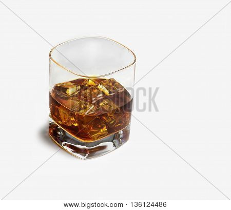 Closeup of a glass of whisky with ice cubes on light background