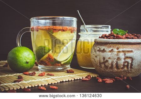 Fresh antioxidant herbal tea from goji berries lime and honey in a glass cup. Wolfberry for a healthy diet. Healthy food. Alternative medicine. Recovery. Rejuvenation. Slimming. Mystic light style.