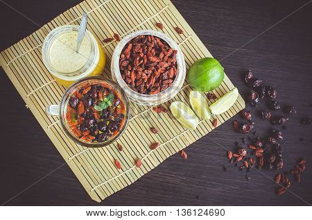 Fresh antioxidant herbal tea from dried goji berries sweetbrier and blueberry in a glass cup on wooden background with lime and honey. Healthy food. Alternative medicine. Top view.Mystic light style.