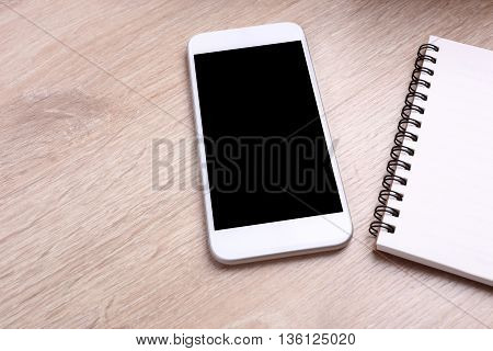 Blank screen smartphone and notebook on wooden background