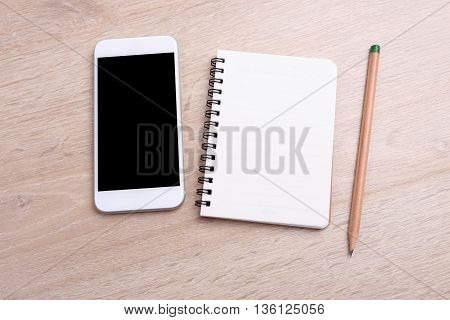 Blank screen smartphone with notebook and pencil on wooden background