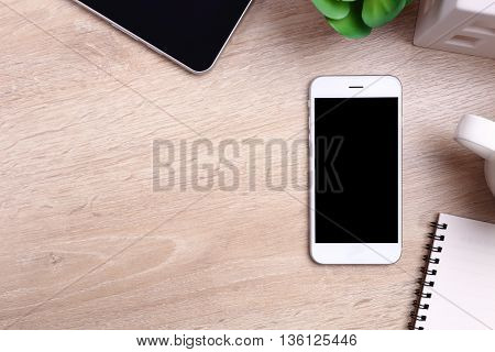 Blank screen smartphone tablet and office supplies on wooden background
