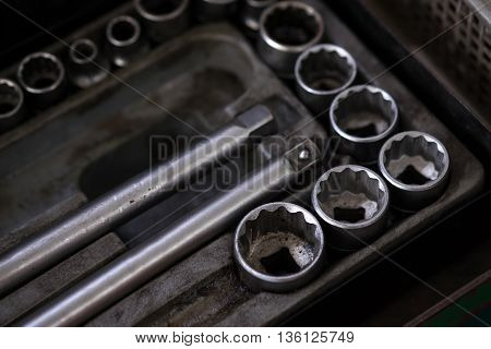 Tools for use with nuts. Metal Work. Box wrench head bits for the screwdriver and other tools on a dark background