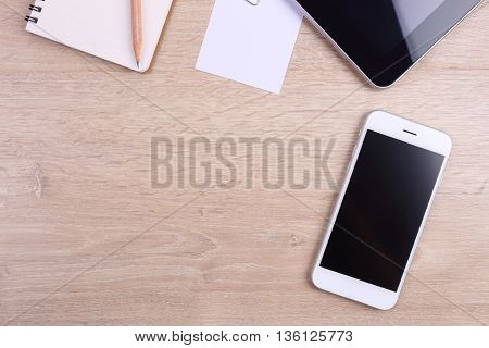 Top view smartphone tablet and office supplies on wooden background