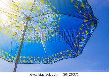 Blue sun umbrella close-up on a background of blue sky