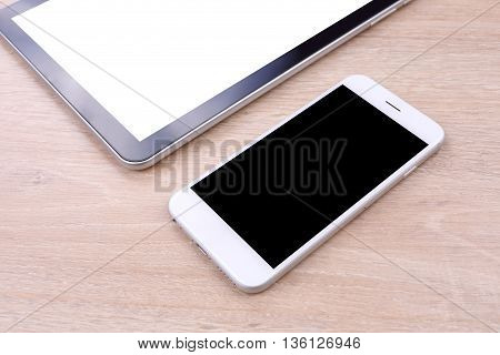 Perspective smartphone and tablet blank screen on wooden background