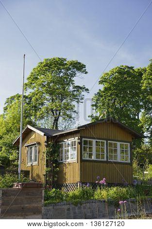 Idyllic yellow cottage in botanical garden in summer.