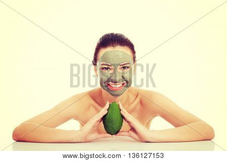 Beautiful woman with facial mask holding avocado.