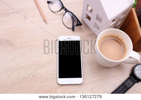 Blank screen smartphone glasses and office supplies on wooden background