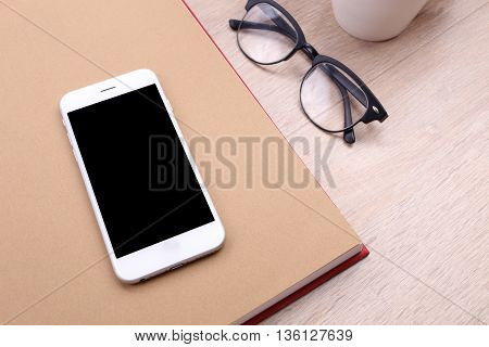 smartphone on book and glasses on wooden background