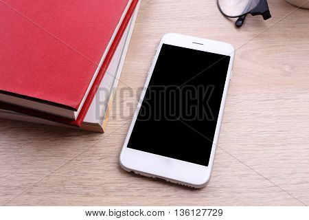 smartphone and red book on wooden background