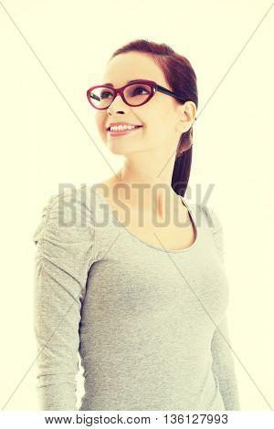 Portrait of beautiful woman in eyeglasses looking up.