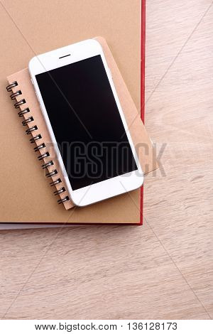 top view smartphone on book and glasses on wooden background