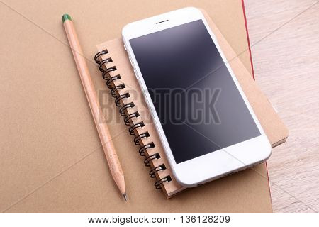 Smartphone with pencil on book and wooden background