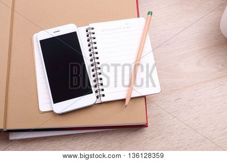 Blank screen smartphone with pencil and note book on wooden background