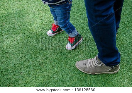 Walking toddler concept. First steps. Foot of father and son in stylish sneakers on the background of green grass. Father's Day. Happy Fathers Day. Happy family. Father and baby. Copy space.