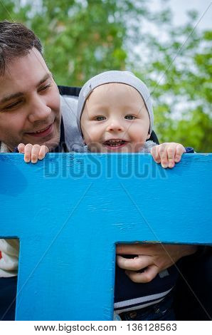 Father with son having fun in playground. Smiling father and baby boy on playground. Father and toddler hugging and playing together outdoors. Father hugs his son. Happy family on playground.