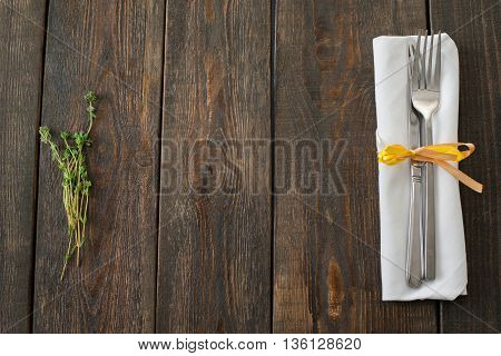 Cutlery and rosemary on dark wood copyspace flat lay. Top view on dark wooden table with rosemary bunch and white napkin with fork and knife on the sides of picture. Cuisine background.