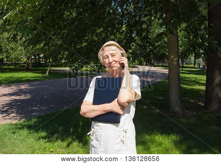 Senior woman with laptop using a mobile phone in park